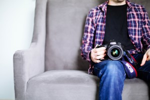 A person sitting on a couch with a camera on his knee.