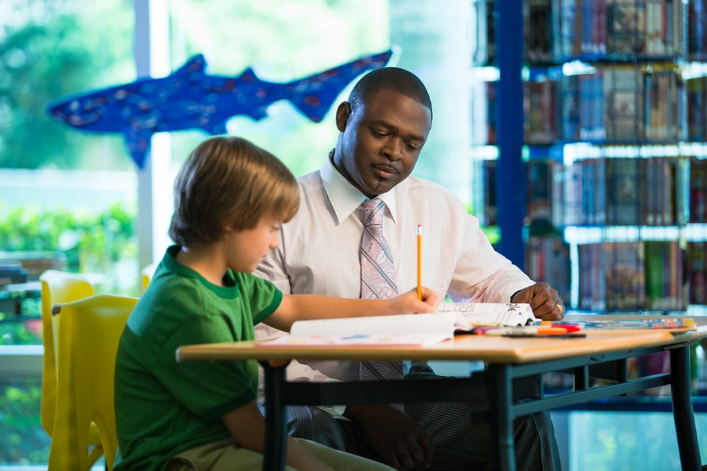 An adult and child sitting in the public library doing homework.