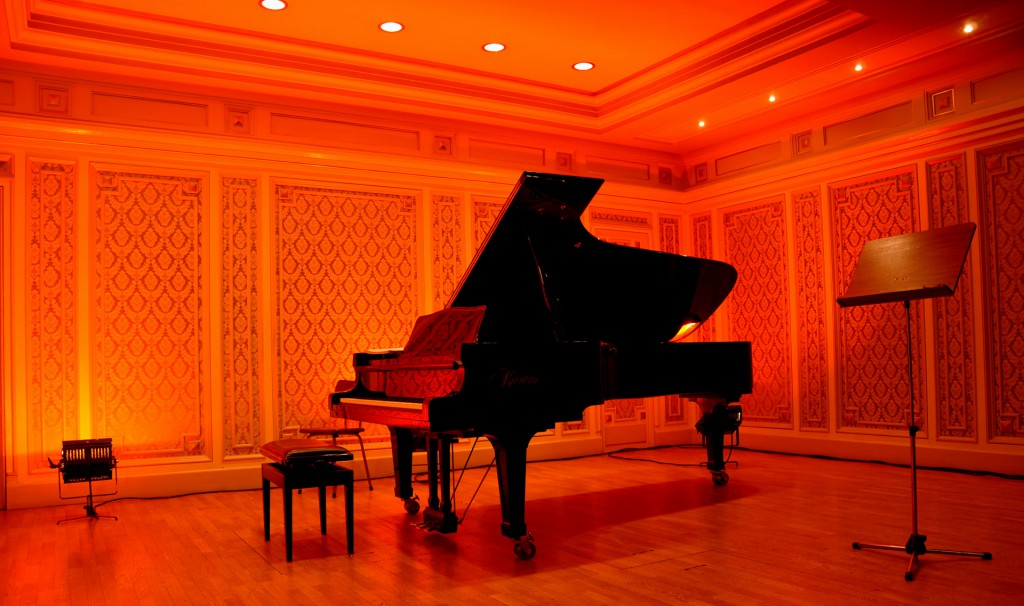 A piano in a red-lit room.